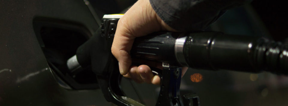 A person refilling their car with gasoline